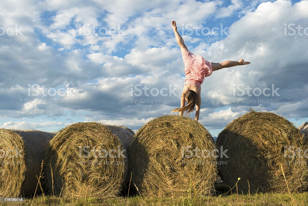 Young Woman Doing Cartwheel on Bales of Grass royalty-free stock photo