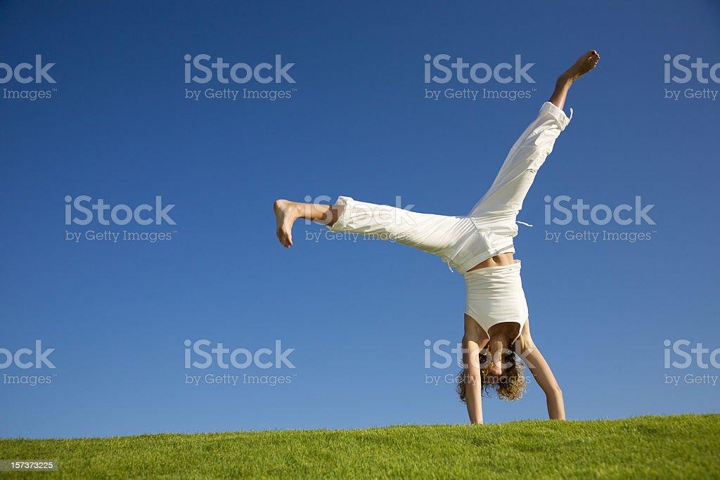 Young woman doing cartwheel on grass stock photo