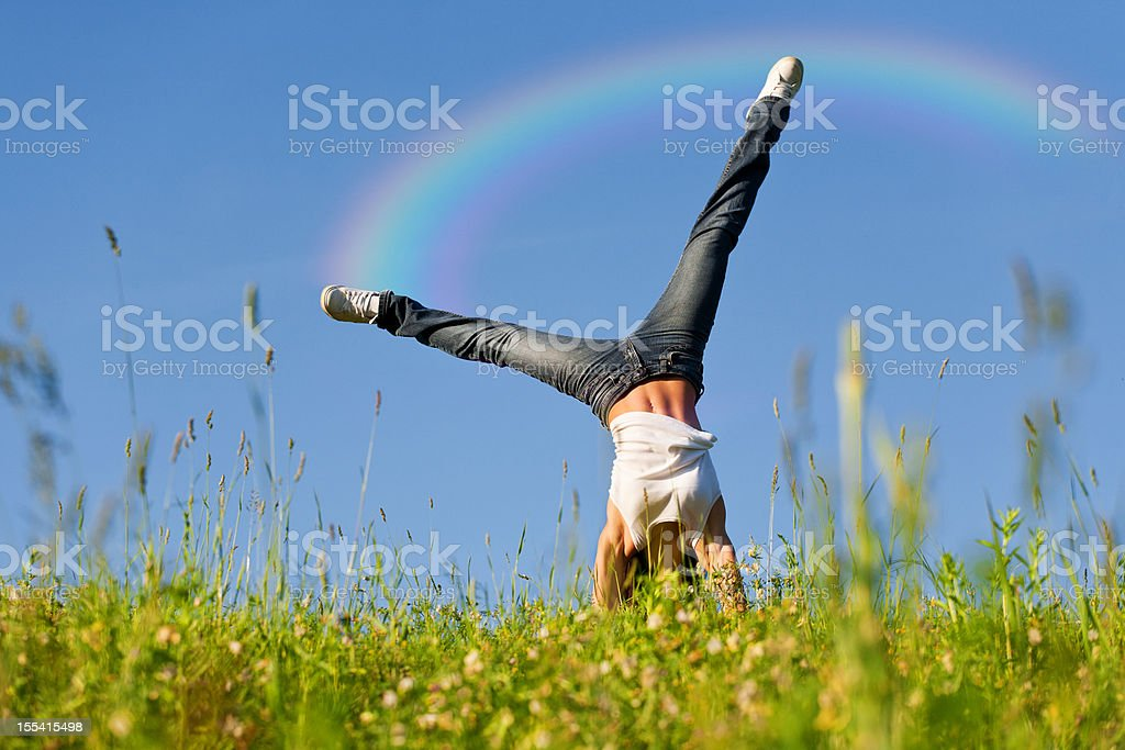 Young woman doing cartwheel with rainbow behind stock photo