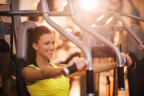 Junge Frau, die Brust-Übungen, die auf Übung Maschine im Fitnessstudio. – Foto
