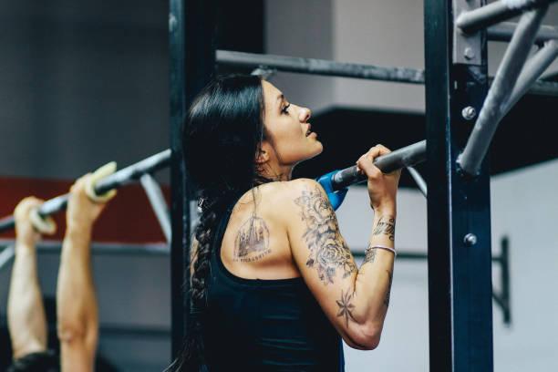 junge frau tun klimmzüge am crosstraing-ausbildung - gymnastik tattoo stock-fotos und bilder