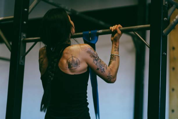 junge frau auf klimmzüge zu tun - training - gymnastik tattoo stock-fotos und bilder