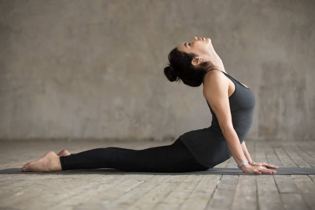 Young woman doing Cobra exercise Young woman practicing yoga, doing Cobra exercise, Bhujangasana pose, working out, wearing sportswear, black pants and top, indoor full length, gray wall in yoga studio cobra pose stock pictures, royalty-free photos & images