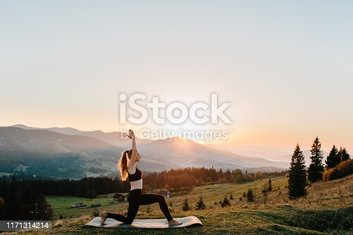 Young woman doing complex Hatha Yoga exercise with Namaste asana. Amazing Yoga plank pose outdoors landscape in beautiful mountains.