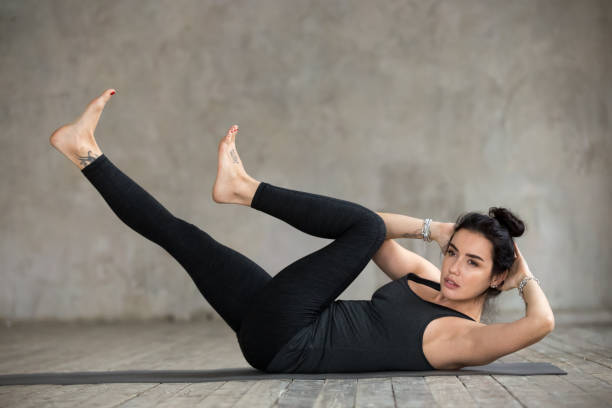 young woman doing crisscross exercise - sit ups stock photos and pictures