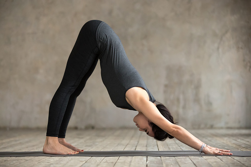 Young Woman Doing Downward Facing Dog Exercise Stock Photo ...