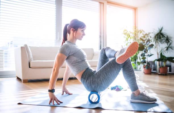Mujer joven haciendo ejercicio en su hogar. - foto de stock