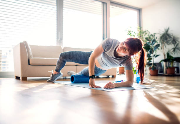 Young woman doing exercise at home. stock photo
