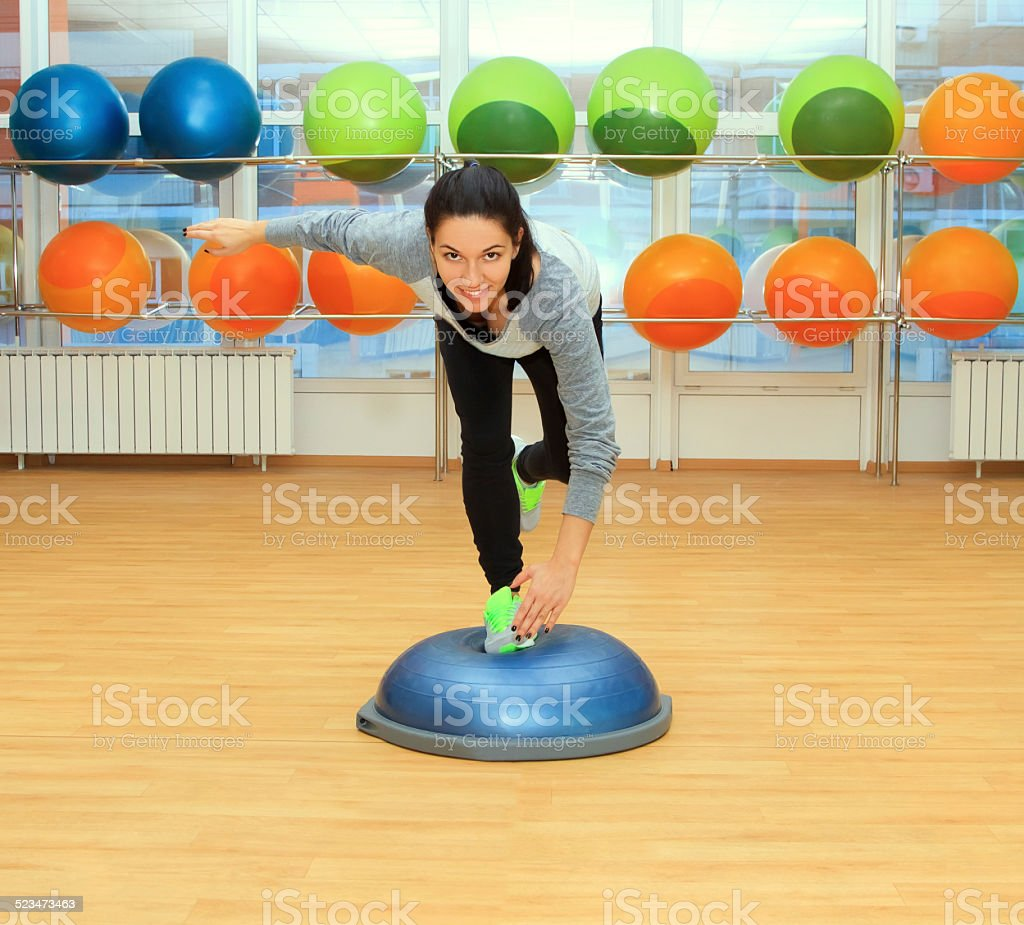 Young woman doing exercise on bosu ball stock photo