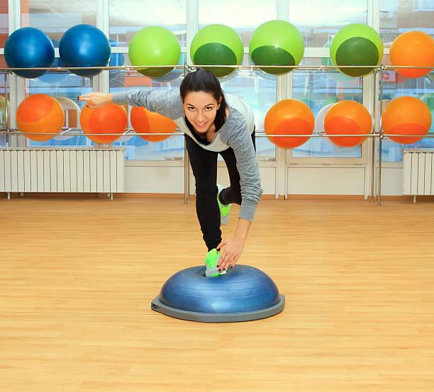 Young woman doing exercise on bosu ball stock photo