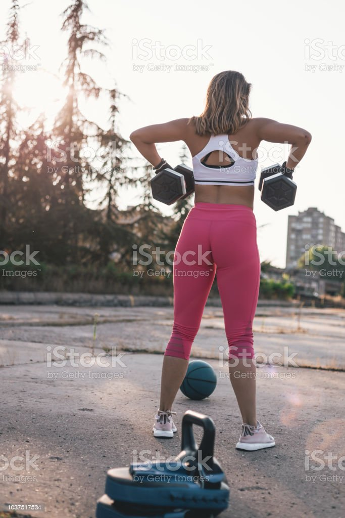 Young woman doing exercise outside with dumbbell stock photo