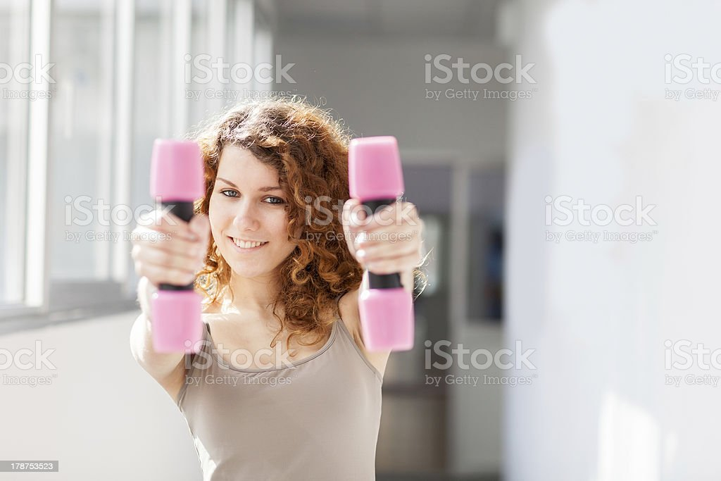 Young woman doing exercise with dumbbells stock photo