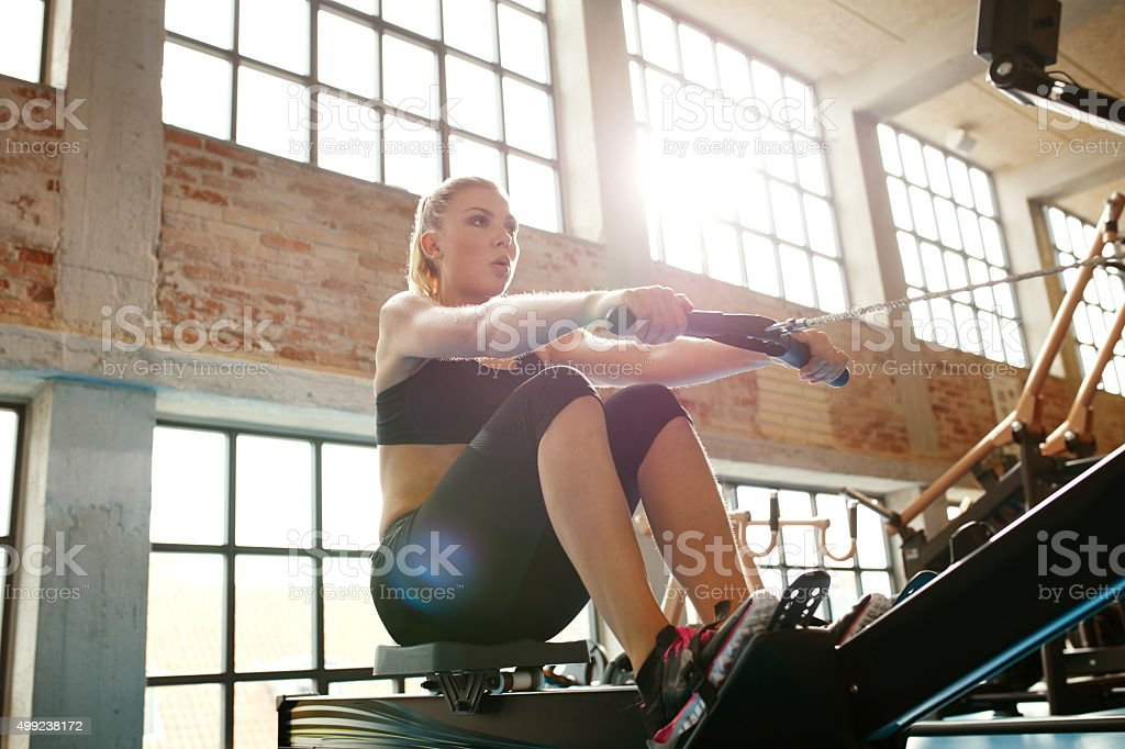 Young caucasian woman doing exercises on fitness machine in gym....