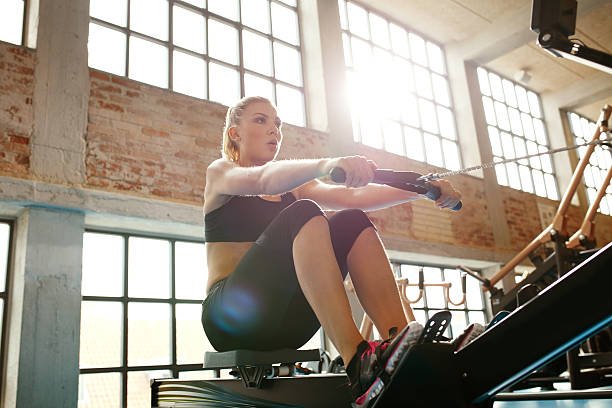 Young woman doing exercises on fitness machine Young caucasian woman doing exercises on fitness machine in gym. Female using rowing machine at  fitness club. exercise machine stock pictures, royalty-free photos & images