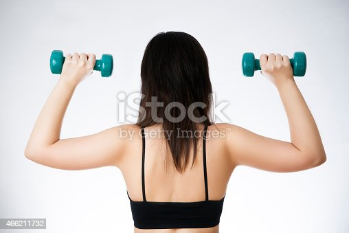 istock Young woman doing exercises with dumbbells 466211732