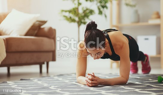 istock young woman doing fitness and sports at home 1151044509