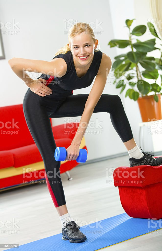 Young woman doing fitness exercises with dumbbells at home royalty-free stock photo