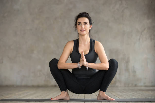 Young woman doing Garland exercise Young sporty woman practicing yoga, doing Garland exercise, Malasana pose, working out, wearing sportswear, black pants and top, indoor full length, gray wall in yoga studio groyne stock pictures, royalty-free photos & images