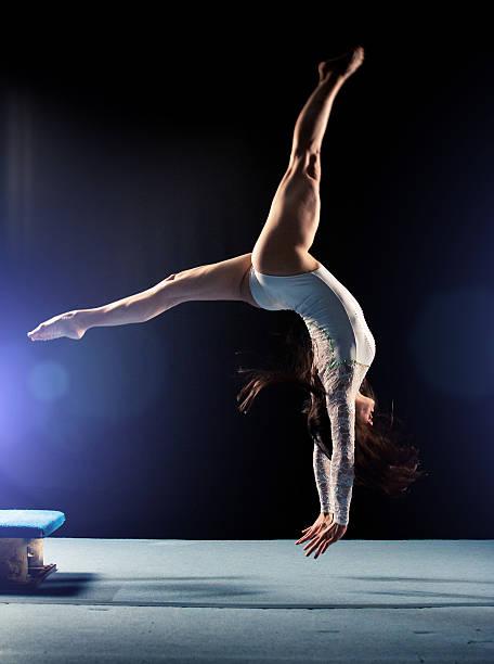 Young woman doing gymnastics jump stock photo