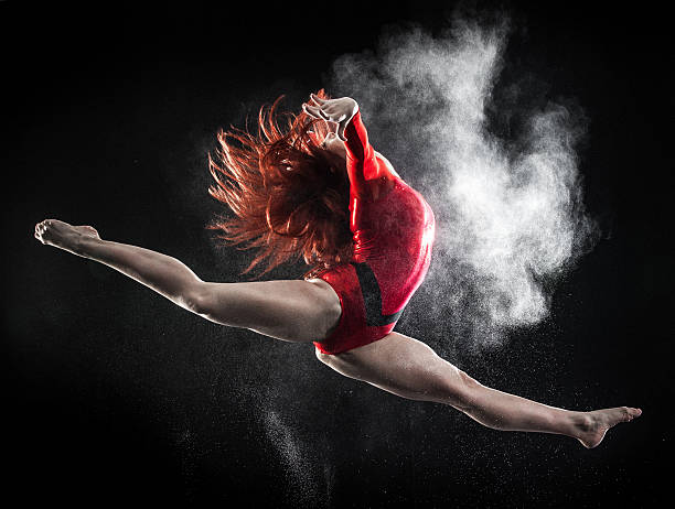 young woman doing gymnastics jump - gymnastics stock pictures, royalty-free photos & images