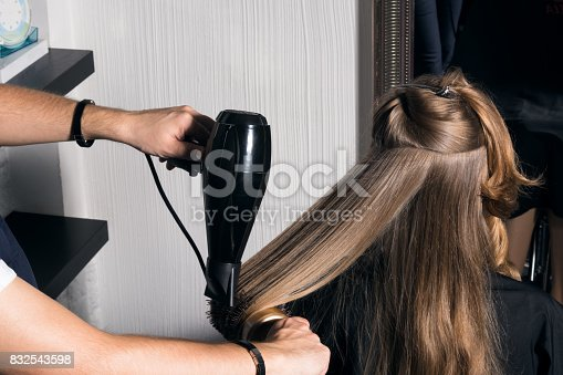 Young woman doing hair styling in the salon. The hairdresser combs her hair.