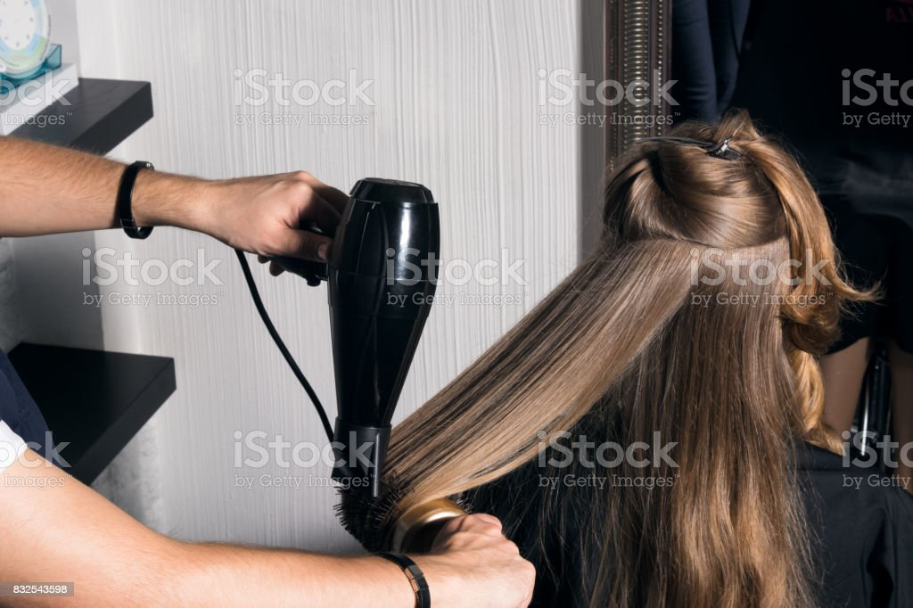 Young woman doing hair styling in the salon. stock photo
