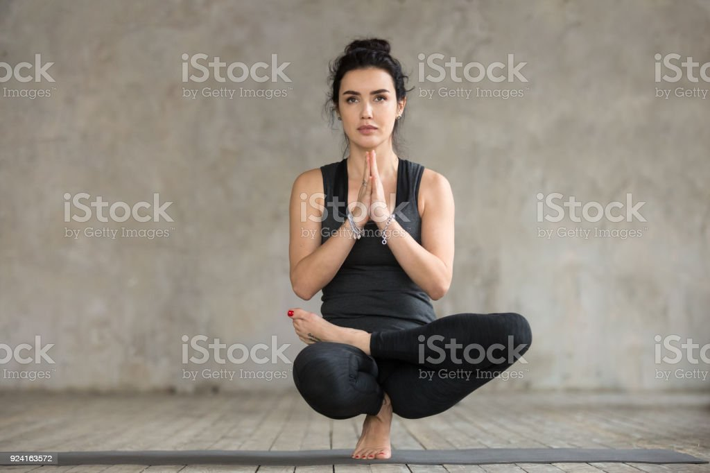 Young woman doing Half Lotus Toe Balance exercise stock photo