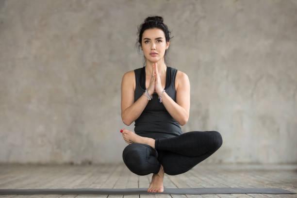 Young woman doing Half Lotus Toe Balance exercise stock photo
