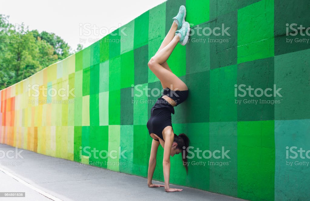 Young woman doing handstand on city street royalty-free stock photo
