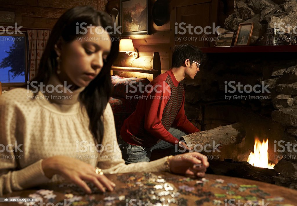 Young woman doing jigsaw puzzle, man putting logs on fire royalty-free stock photo