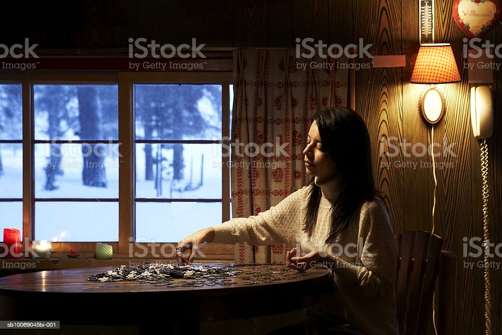 Young woman doing jigsaw puzzle royalty free stockfoto