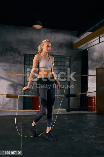 Young woman doing jumping rope warming up exercise before boxing on squared ring