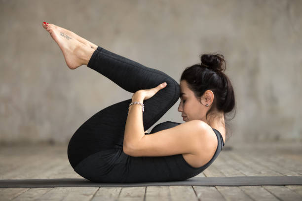 Young woman doing Knees to Chest exercise Young sporty woman practicing yoga, doing Knees to Chest exercise, Apanasana pose, working out, wearing sportswear, black pants and top, indoor full length, gray wall in yoga studio apanasana stock pictures, royalty-free photos & images