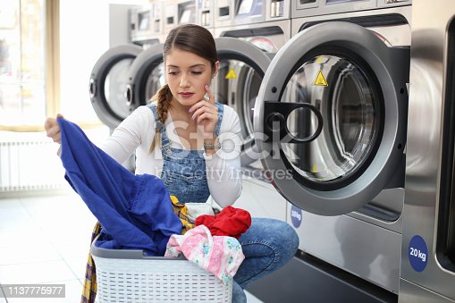 Young woman doing her laundry at a laundromat. About 25 years old, Caucasian female.