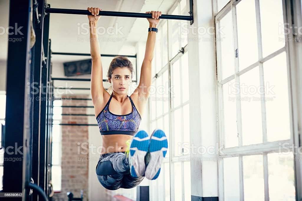 Young woman doing leg raises on pull-up bar in gym stock photo