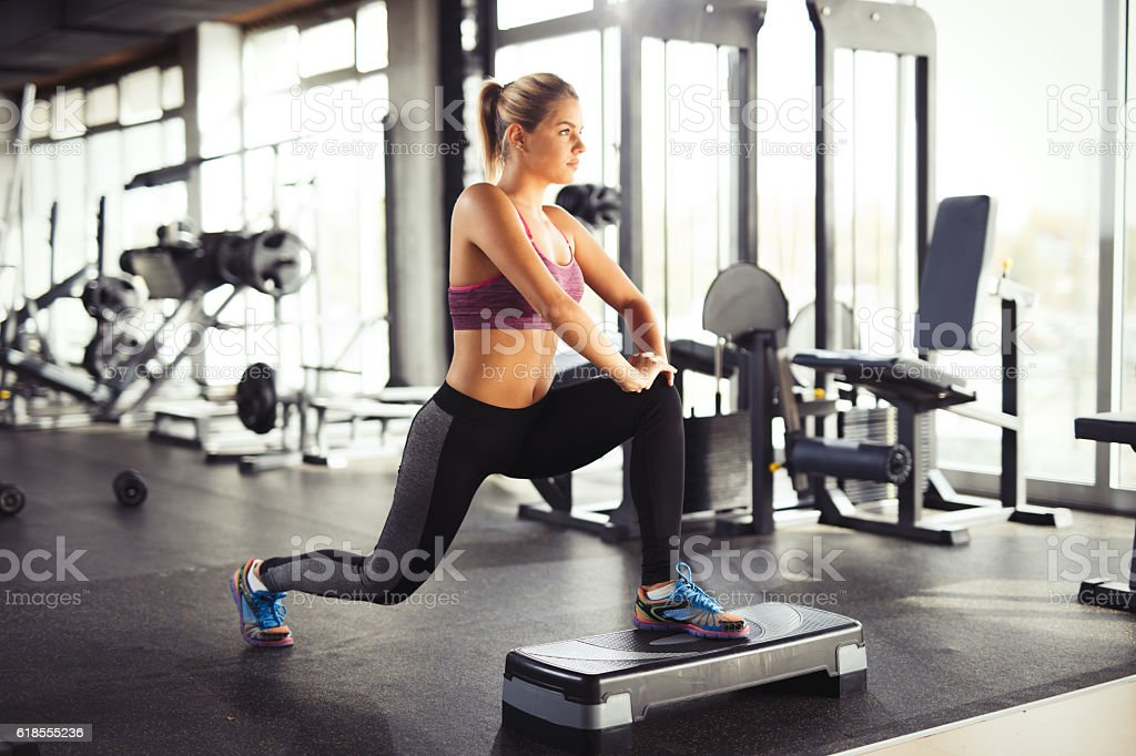 Young woman doing lunges on step aerobics equipment at gym. stock photo