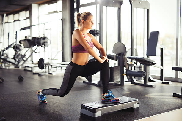 young woman doing lunges on step aerobics equipment at gym. - lunge stock photos and pictures
