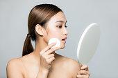 若い女性が化粧をしています。肌ケアのコンセプトです。