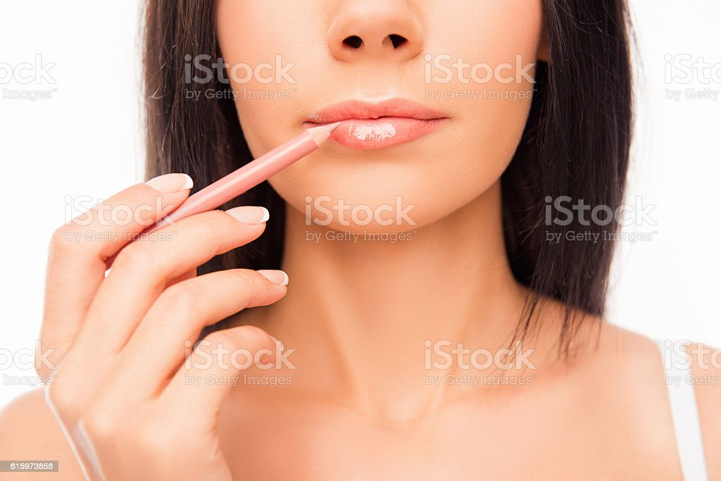 Young woman doing maquillage with lip's liner, close up photo stock photo