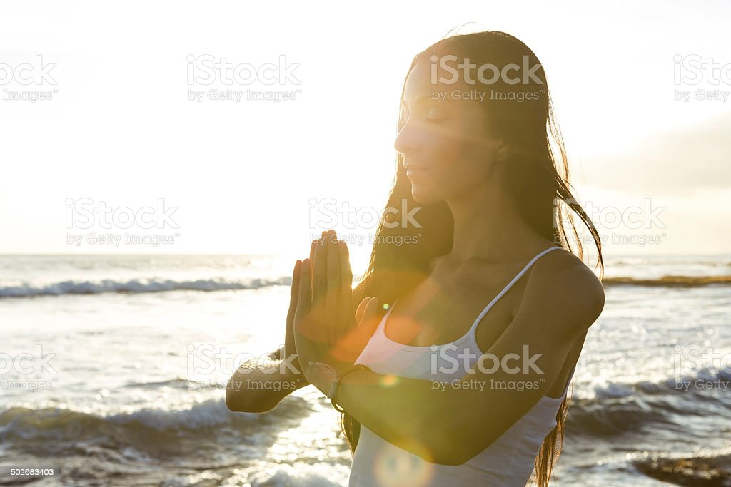 Young woman doing meditation at sunset stock photo