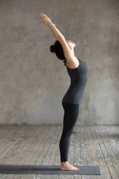Young woman doing mountain exercise Young woman practicing yoga, doing mountain exercise, Tadasana pose, working out, wearing sportswear, black pants and top, indoor full length, gray wall in yoga studio. Side view photo sun salutation stock pictures, royalty-free photos & images