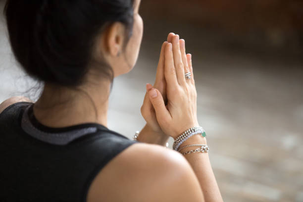 Young woman doing namaste gesture, closeup Namaste gesture close up photo, young attractive woman practicing yoga, working out, wearing wrist bracelets and rings, indoor, yoga studio, behind the shoulder view. Contemplation concept prayer pose yoga stock pictures, royalty-free photos & images