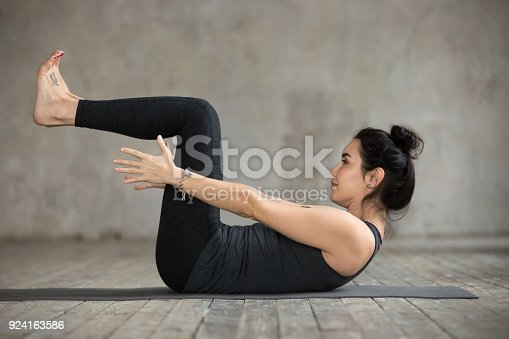 914755474 istock photo Young woman doing navasana exercise 924163586