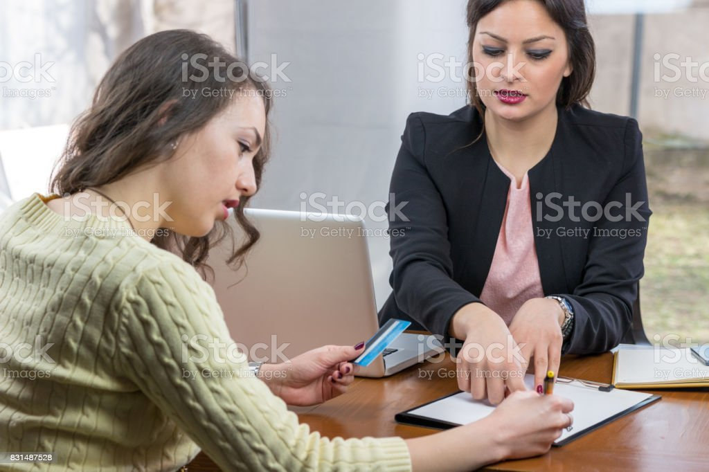 Young woman doing paperwork with bank advisor in an office. stock photo