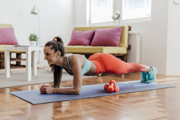 young woman doing plank exercise in her home - milan2099 stock photos and pictures