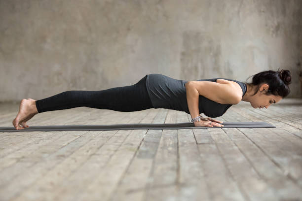 Young woman doing Push ups or press ups Young woman practicing yoga, doing four limbed staff, Push ups or press ups, exercise, chaturanga dandasana pose, working out, wearing sportswear, black pants, top, full length, gray wall in studio namaskard geothermal area stock pictures, royalty-free photos & images
