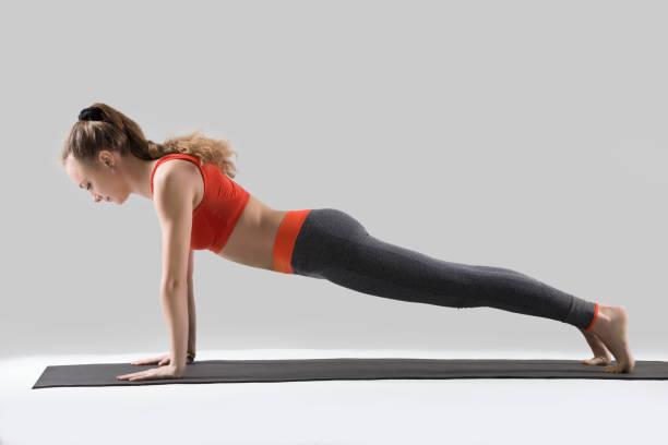 young woman doing push ups or press ups, studio - peso mosca foto e immagini stock