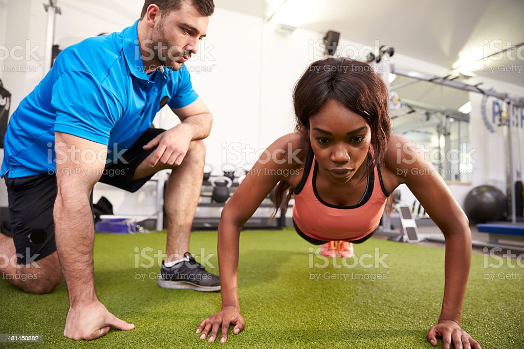 Young woman doing push ups under supervision of a trainer stock photo