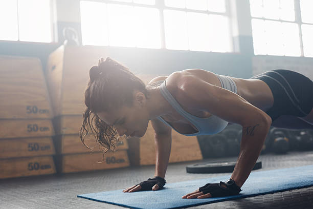Young woman doing push-ups at the gym stock photo