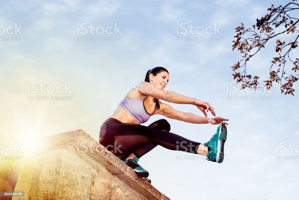 Young woman doing single leg squats stock photo